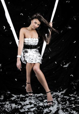 Attractive girl sitting in a hinged swing. White feather-bed flying in a shot with a dark background.  photo