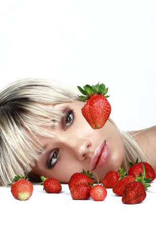 Glamour portrait of the attractive woman surrounded ripe strawberry. Isolated on white.  photo