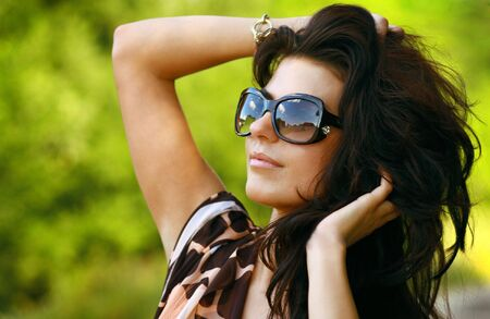 Beautiful young black hair woman in sunglasses walking in summer park. photo
