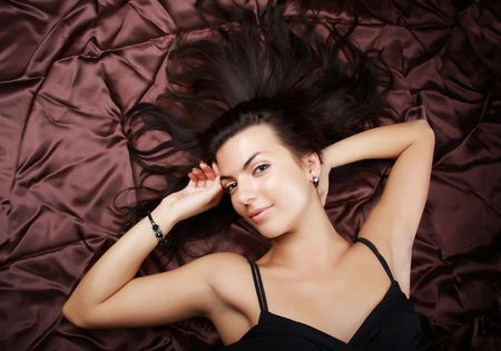 Glamour lady with long hair laying on a brown background. Close-up face  photo