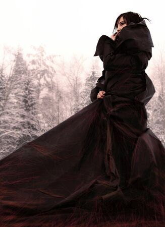 wicca: mysterious girl in a long black dress on snow.