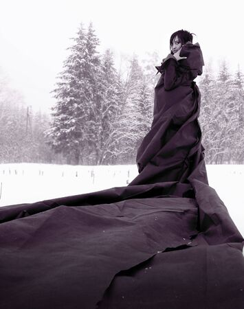 folds: mysterious girl in a long black dress standing on snow.