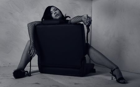 The sexual girl sitting in an armchair from car with bottle of poisoning photo