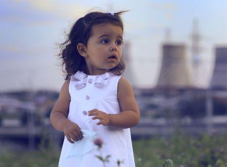 descendants: Little girl against power station. Stock Photo