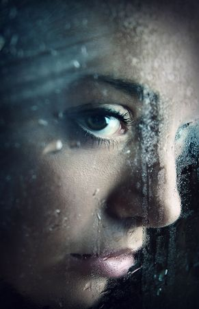Young girl looking through window after rain. Close-up portrait. photo