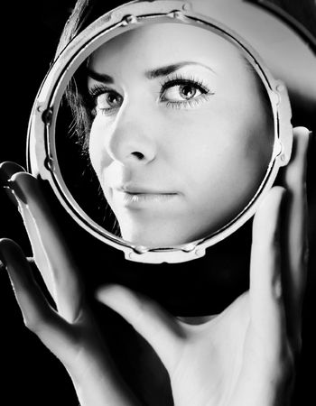Bewitching portrait of beautiful girl looking through spherical metal capacity.  photo
