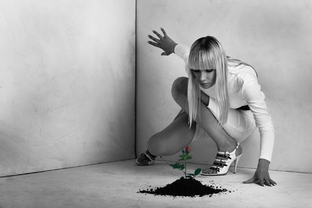 agrarian: Elegant beauty in a white room near to a flower growing from a floor. Conceptual art