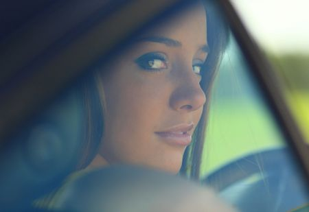 Portrait of girl through automobile glass.  photo