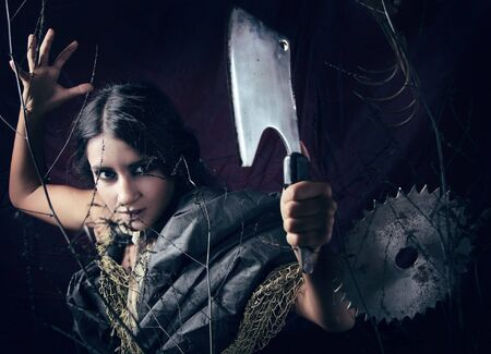 demoniacal: Stylised witch in bushes and dangerous sharp tools. Halloween photo.  Stock Photo