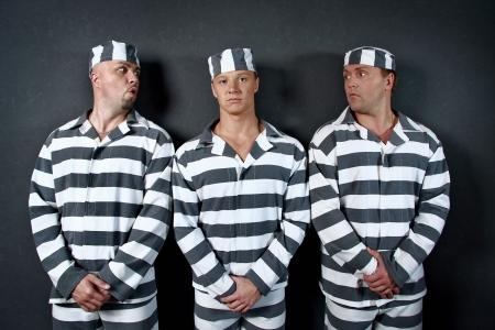 Drei Häftlinge. Gruppe der Männer in Anzügen von Strafgefangenen.