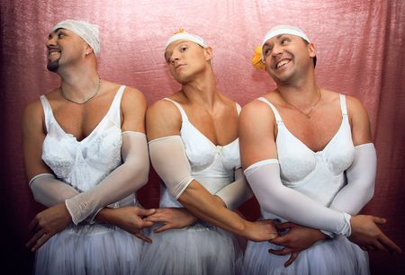 Three strong men in suits of ballerinas. Ñomic photo on a pink background.