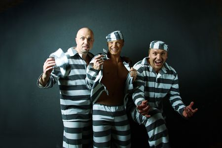 concluded: Three prisoners. Group of men in suits of convicts. Stock Photo