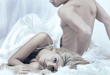 couple lit: Fille de la d�ception se trouve sur un lit avec des jeunes gars stitting Banque d'images