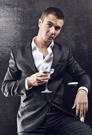 lounge: A young handsome businessman drinking a martini