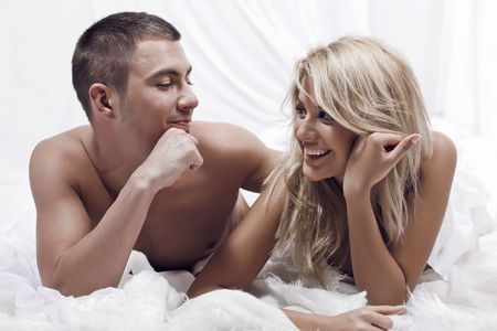 man lying down: Beautiful young couple in the bedroom