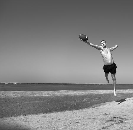 Young men playing football on beach photo