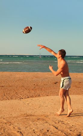 Young men playing football on beach