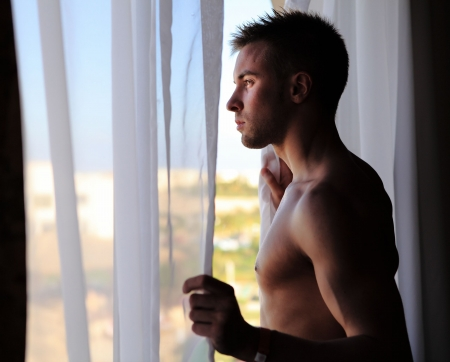 Young attractive macho looking in window Stock Photo