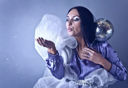 Beautifull woman stylised on club fairy blowing off from palm silver spangles. Fashion Photo. photo