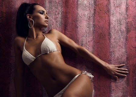 Dramatic lighting shot of a beautiful&sexy woman with lingerie on a pink background.
