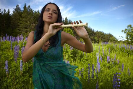 Attractive girl with a flute sitting in a summer field. Photo. Stock Photo - 7395889