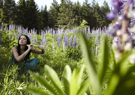 Attractive girl with a flute sitting in a summer field. Photo. Stock Photo - 7395976