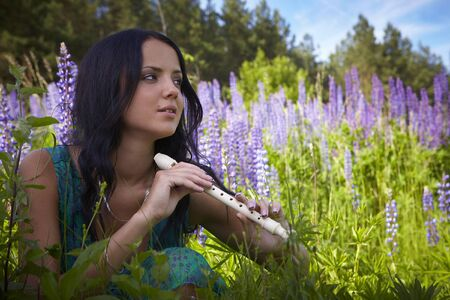 Attractive girl with a flute sitting in a summer field. Photo. Stock Photo - 7395879