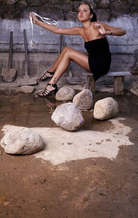 Sexual girl in black dress inside stone quarry among old shovels. Photo. Stock Photo - 7395969