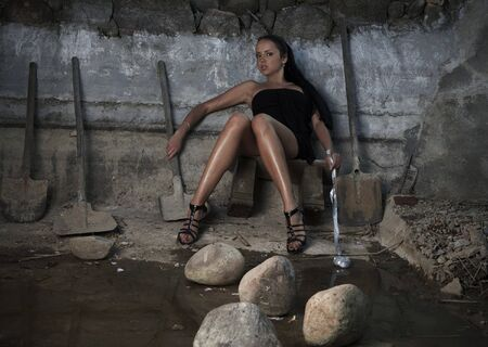 Sexual girl in black dress inside stone quarry among old shovels. Photo. Stock Photo - 7395965