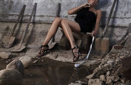 Sexual girl in black dress inside stone quarry among old shovels. Photo. Stock Photo - 7395964