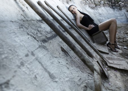 Sexual girl in black dress inside stone quarry among old shovels. Photo. Stock Photo - 7395884