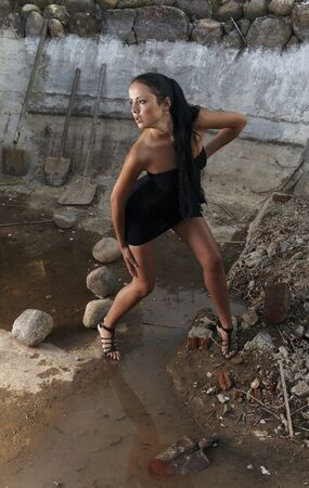 Attractive woman in a stone hole among old shovels. Photo. Stock Photo - 7395974