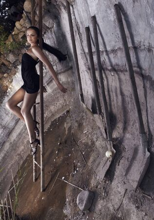 Sexual girl laying on a rusty ladder of leader in a concrete foundation ditch with set of old shovels. Photo. Stock Photo - 7395981