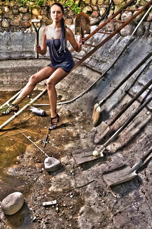 Attractive woman in a stone hole among old shovels. HDR style Photo. photo