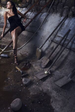 Attractive woman in a stone hole among old shovels. Photo. Stock Photo - 7395972