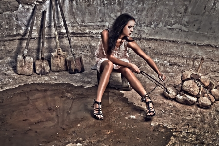Attractive prisoner in a pink dress saws a file a chain on a foot. Vogue style HDR photo. Stock Photo - 7395986