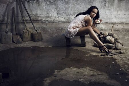 Attractive prisoner in a pink dress with billiard ball in hands. Vogue style photo. photo
