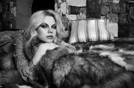 Blonde a relaxa near a fireplace laying on fox skins. B&W photo.  photo