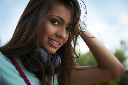 Young beautiful girl with earphones smiling.  photo