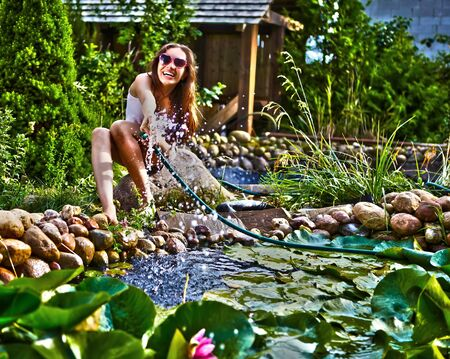 streamlet: Happy young female with Garden streamlet relaxing near the pond. HDR style.  Stock Photo