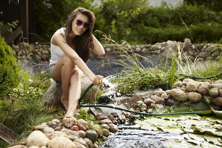 streamlet: Happy young female with Garden streamlet relaxing near the pond.