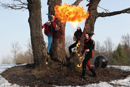 Group of retro fire-eater showing fire-show on forest. photo