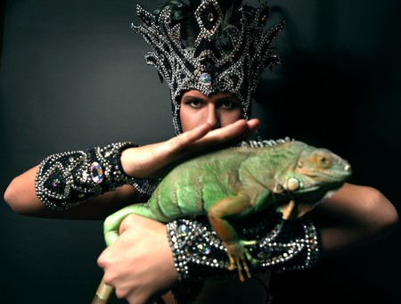 ritual: Young pagan priest in ritual suit with green iguana in his hands