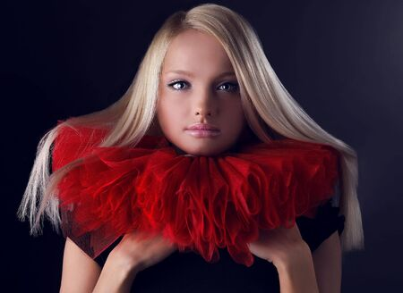 jabot: Attractive blond beauty in a red theatrical jabot. Close-up Portrait.  Stock Photo