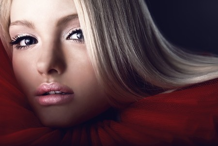 Attractive blond beauty in a red theatrical jabot. Close-up Portrait.  photo