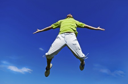 Jumping up guy in a green shirt against blue sky.  photo