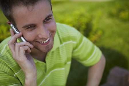 cheerful guy in a green vest speaks by phone.  photo