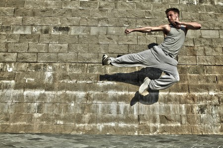 Young attractive man dancing in urban background  photo