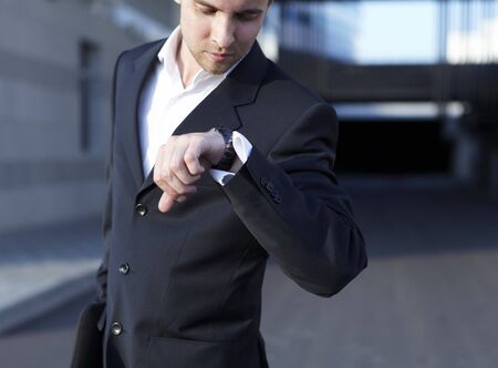 A handsome business man looking at watch photo