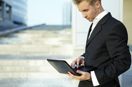 Closeup portrait of young businessman using laptop on street